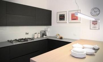 Cucina nera con top in Laminam grigio.